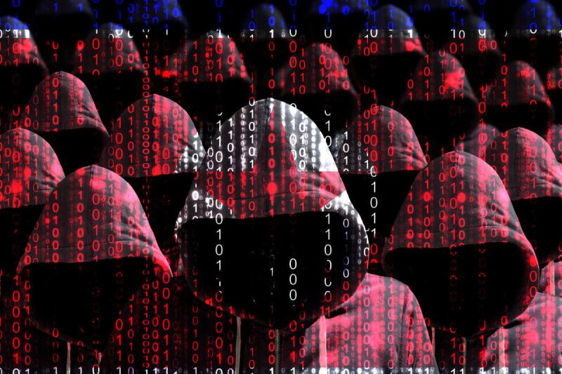Group of hooded hackers shining through a digital north korean flag